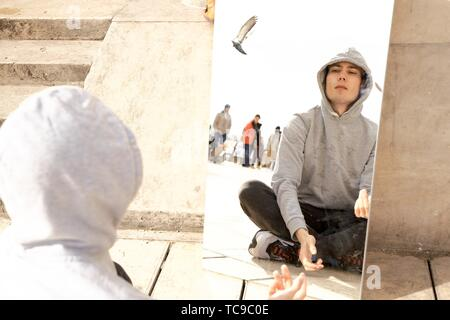 hopeful young man looking at his mirror image in public, in Paris, France. - Stock Photo