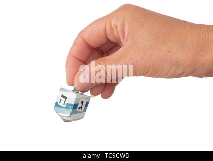 Woman spinning a dreidel isolated on white background. Visible Hebrew letters show Hei, meaning half, and Gimmel, meaning all. - Stock Photo