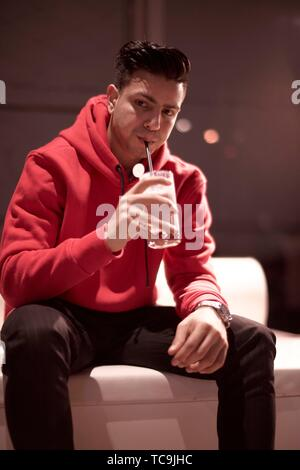 man drinking long drink with drinking straw, sitting indoors in bar, Afghan ethnicity, in Munich, Germany - Stock Photo