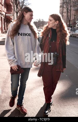 couple walking hand in hands outdoors in sunlight at street in city, in Berlin, Germany - Stock Photo
