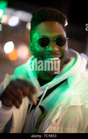 young happy laughing African man in green lights at night, wearing sunglasses, in Munich, Germany
