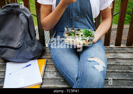 Midsection portrait of a student girl sitting in a bench while eating healthy salad with pasta in a glass lunch box - Stock Photo