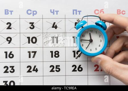 A hand holds a small alarm clock, in the background is a calendar with the day marked and the word vacation. - Stock Photo