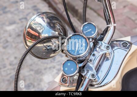 Close up of classic motorcycle shinny handlebar and chrome motorcycle speedometer on a street. - Stock Photo