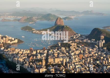 Late evening view over Rio de Janeiro from the Christ the Redeemer statue on top of Corcovado mountain. Favela in the lower left corner in the shade. - Stock Photo