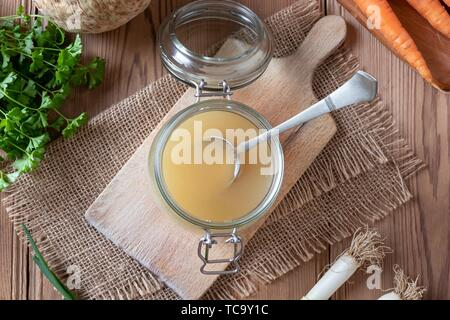 Glass jar with chicken bone broth, top view. - Stock Photo