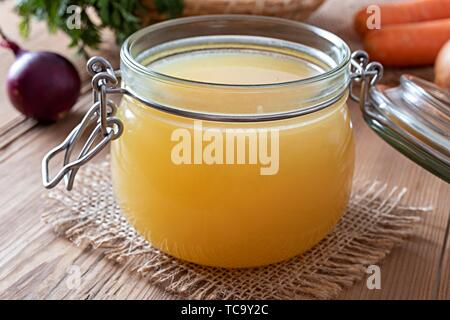 Chicken bone broth in a glass jar, with onions and carrots in the background. - Stock Photo