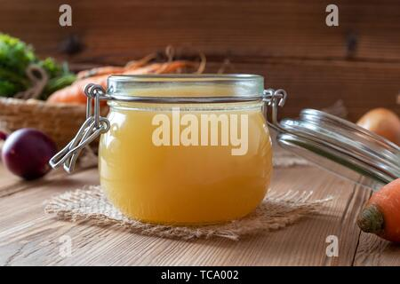 Chicken bone broth in a glass jar, with fresh vegetables in the background. - Stock Photo