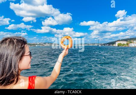 Beautiful Chinese woman holds traditional Turkish simit (bagel) with view of Bosphorus in Istanbul,Turkey. - Stock Photo