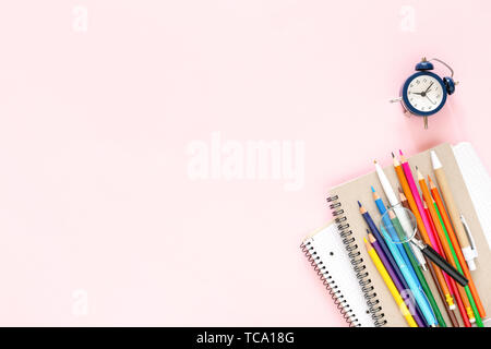 School stationary on pink background. Notebooks, pens, color pencils and alarm clock. Back to School concept. - Stock Photo