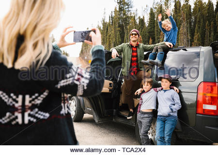 Mother with camera phone photographing husband and sons at roadside - Stock Photo