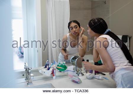 Teenage girl applying makeup at bathroom mirror - Stock Photo