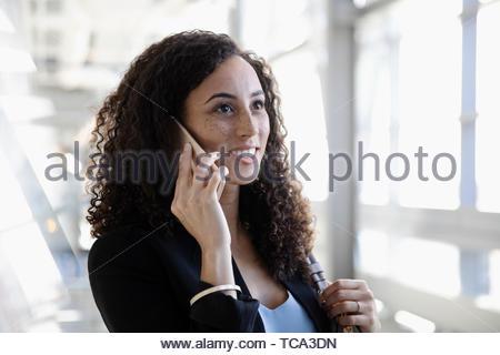Smiling businesswoman talking on smart phone - Stock Photo