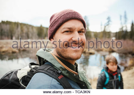 Portrait smiling confident man hiking with son in woods - Stock Photo