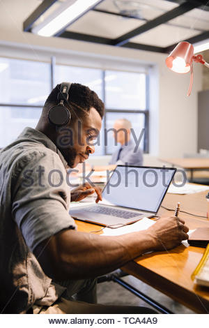 Focused creative businessman with headphones working at laptop in coworking space - Stock Photo