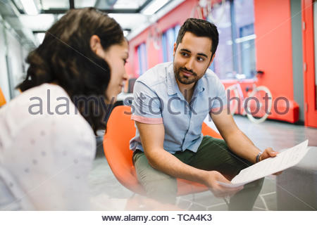 Business people discussing paperwork in office meeting - Stock Photo