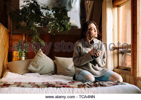 Serene woman with coffee relaxing on cabin bed - Stock Photo