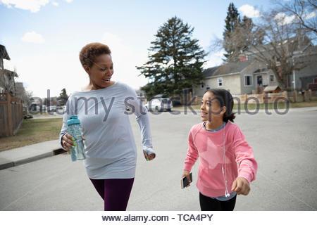 Grandmother and granddaughter exercising, walking in neighborhood - Stock Photo