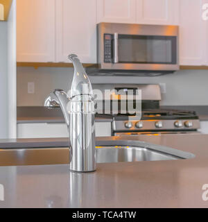 Frame Square Modern kitchen interior with close up on the shiny faucet and sink