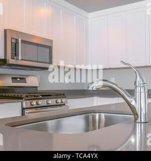 Square Close up of a glossy countertop with faucet and sink inside a modern kitchen