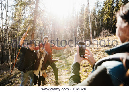 Woman with camera phone photographing happy friends hiking in sunny woods - Stock Photo