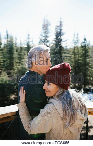 Affectionate couple hugging on sunny balcony - Stock Photo