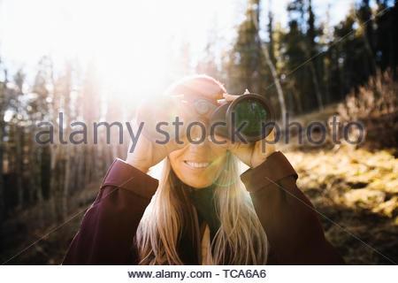 Portrait smiling woman with binoculars bird watching in sunny woods - Stock Photo