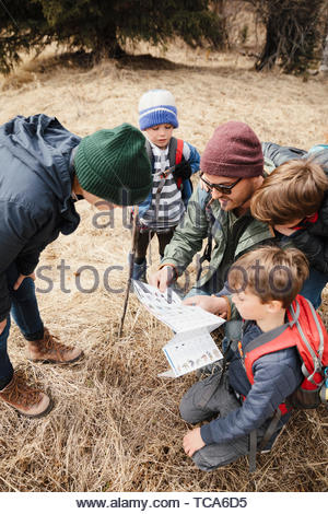 Family with guide map hiking in woods - Stock Photo