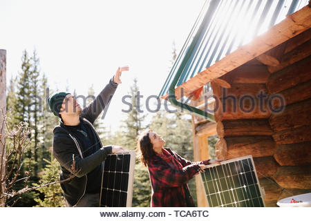 Couple installing solar panels on cabin - Stock Photo