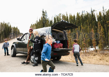Family standing and playing outside car at remote roadside - Stock Photo