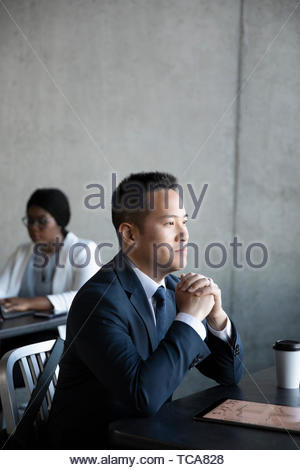 Ambitious, forward looking businessman at cafe table - Stock Photo