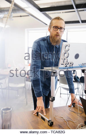 Portrait confident businessman working at laptop at sit-stand desk - Stock Photo