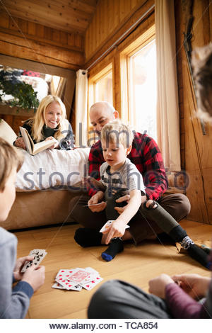 Family reading and playing cards in cabin - Stock Photo