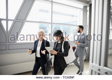 Business people walking and talking in office corridor - Stock Photo
