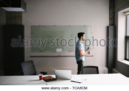 Thoughtful businessman looking out office window - Stock Photo