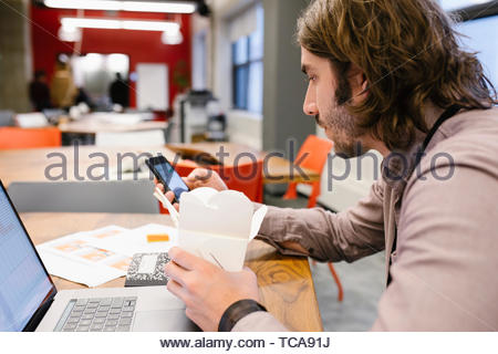 Businessman working late, eating take out food in office - Stock Photo