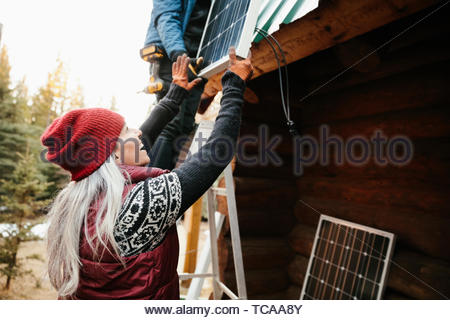 Happy woman installing solar panels on cabin - Stock Photo