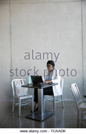Businesswoman working at laptop in cafe - Stock Photo