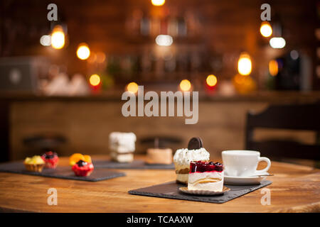 Composition of different cakes with tasty flavours over a wooden table in a coffee shop. Tasty mini cakes with fruits. Cakes with delicious biscuit on top. - Stock Photo