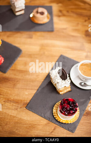 Top view photo of cake with tasty biscuit near different mini cakes on a wooden table in a coffee shop. Delicious cake with tasty fruits on top and coffee cream. - Stock Photo