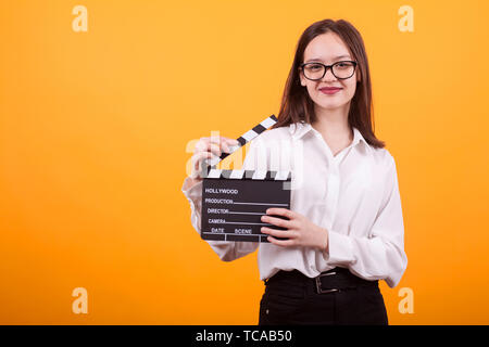 Charming little girl holding clappers, looking at camera and smiling, standing on yellow background. Cheerful teenage girl with cinema board in hands. Pretty caucasian girl smiling to the camera. - Stock Photo