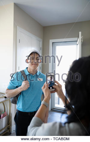 Mother with camera phone photographing teenage son in work uniform - Stock Photo