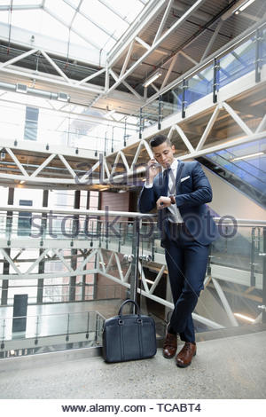 Young businessman talking on smart phone and checking the time on wristwatch on office atrium balcony - Stock Photo