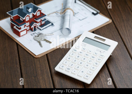 The calculator is placed before the house model and drawing of the villa, and the concepts of real estate transaction, accounting, evaluation, house purchase, house price, etc. - Stock Photo