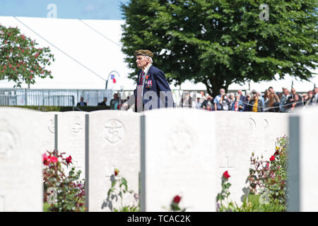 A veteran walks past the graves of fallen soldiers during the Royal British Legion's Service of Remembrance, at the Commonwealth War Graves Commission Cemetery, in Bayeux, France, as part of commemorations for the 75th anniversary of the D-Day landings. - Stock Photo