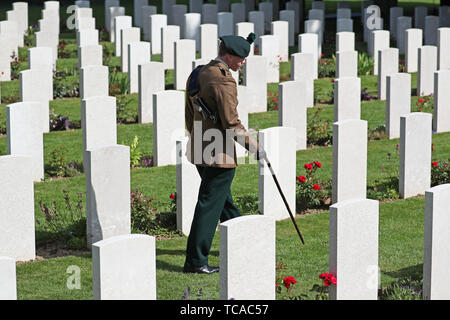 A man in uniform walks past the graves of fallen soldiers during the Royal British Legion's Service of Remembrance, at the Commonwealth War Graves Commission Cemetery, in Bayeux, France, as part of commemorations for the 75th anniversary of the D-Day landings. - Stock Photo