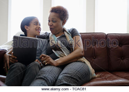Grandmother and granddaughter using digital tablet on sofa - Stock Photo