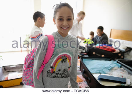Portrait smiling, confident girl helping family pack suitcases - Stock Photo