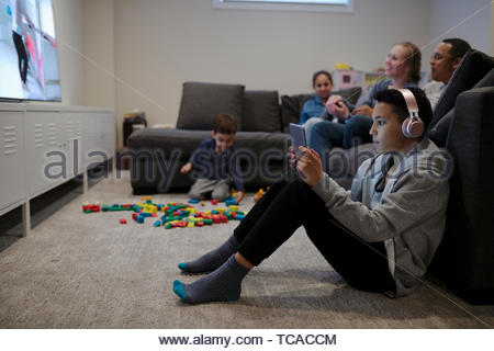 Family playing video game and watching TV - Stock Photo
