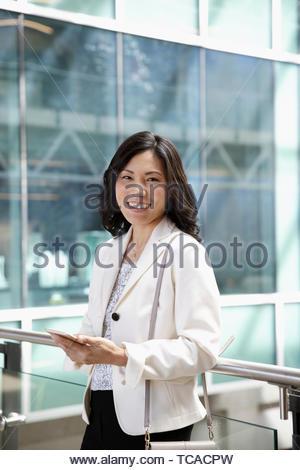 Portrait confident, happy businesswoman using smart phone - Stock Photo